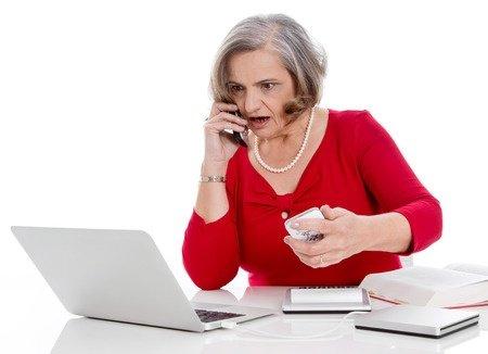 Señora, asustada mientras mira una pantalla de ordenador